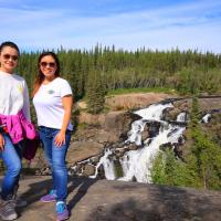 Yellowknife Tours a couple on a hike to Cameron Falls cascading in the back in the NWT.