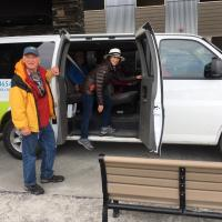 My Backyard Tours tour van with Bill Braden and tourists getting into the van in Yellowknife in the Northwest Territories.