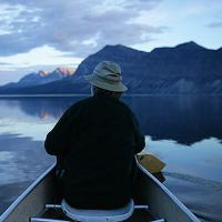 Night Paddling with a man at the helm among the Nahanni Mountains in the Northwest Territories.