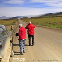 Nature Tours of Yukon Dempster Highway Guided Self-Drive with two visitors in red jackets along a dirt road in the western arctic NWT.