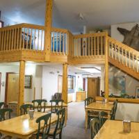Gathering area with tables and chairs and staircase in Grey Goose Lodge in Deline in the Northwest Territories.
