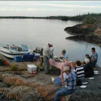 Bluefish Services a group of people eating a shore side fish fry lunch after fishing in Yellowknife Northwest Territories.