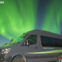 The Northern Star Tourism Services Mercedez Sprinter Van with blazing green aurora in the sky in Yellowknife.