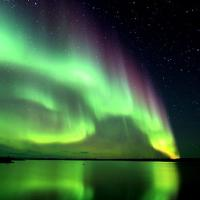 Aurora Borealis green and purple over the lake in Yellowknife captured by Yellowknife Tours in the NWT.