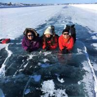 Three people lying on the Dettah Ice Road on a Yellowknife Tours tour in winter in the NWT.