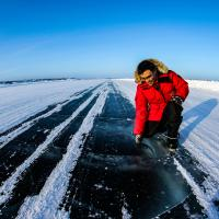 Arctic Tours Canada man in red parka touches the Dettah ice road in Yellowknife NWT.