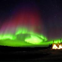 Arctic Tours Canada two glowing teepees at night with the green, purple, and red aurora dancing in the sky in Yellowknife Northwest Territories.