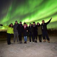 Aurora Ninja Photo Tour group of people standing outside in winter with the green aurora in the sky in Yellowknife, NWT.