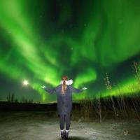 Aurora Ninja Photo Tour a person standing outside in winter with the green dancing northern lights in the sky in Yellowknife, NWT.