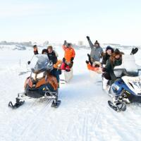 Aurora Ninja Photo Tour people on snow mobiles in snow outside in winter in Yellowknife, NWT.