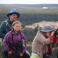 Jackpine Paddle a woman looking through binoculars with her husband and daughter in the background in the Northwest Territories.