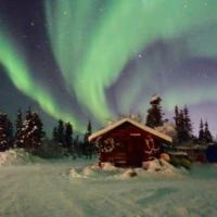Arctic Adventure Tours & Arctic Chalet with the green aurora northern lights over in the sky in winter Inuvik Northwest Territories.