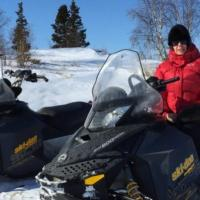TrailBlazer Tours two snowmobiles and a man sitting in one wearing a red parks in winter in Yellowknife, Northwest Territories.