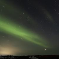 North of 60 Adventures green aurora straight across the dark sky in the Northwest Territories.