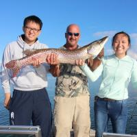 Two Chinese tourists with Great Slave Adventures fishing guide holding up a large fish in the NWT.