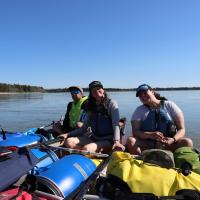 North Star Adventures three people on canoes on an Indigenous culture experience on the Mackenzie River in the NWT.
