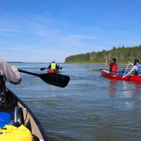 North Star Adventures four people on canoes on an Indigenous culture experience on the Mackenzie River in the NWT.