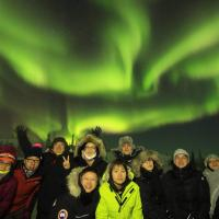 A group of tourists smiling with green aurora behind them in Yellowknife on a North Star Adventures Aurora Hunting tour experience.