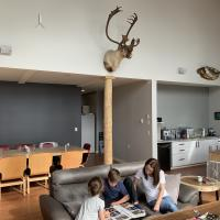 A family sitting on the couch in the main lodge reading in the Northwest Territories.