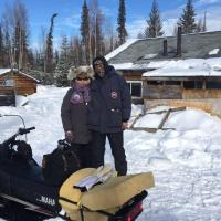 K'iyeli Tourism Services couple by a snowmobile in Fort Simpson in the Northwest Territories