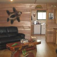 The warm cozy interior of Taltson Lake Lodge with a black couch and wooden furniture in the Northwest Territories.