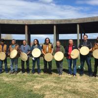A group of Łı́ı́dlı̨́ı̨́ Kų́ę́ First Nation drummers standing side aby side smiling in Fort Simpson in NWT.