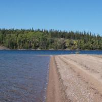 The beach side of Taltson lake Lodge and green trees in the distance in the NWT.