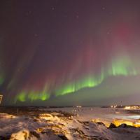 Aurora Dream tours photo of the green and red aurora at Pilot's Monument overlooking the city of Yellowknife.