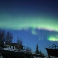 The dancing green and pink aurora above boats on Yellowknife Bay picture by Aurora Dream tours in the Northwest Territories.