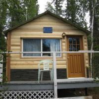 A small yellow cabin at Taltson Lake Lodge surrounded by trees in the NWT.