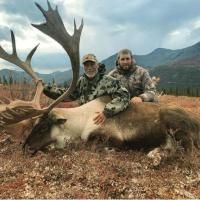 Two men and a caribou they hunted in the Sahtu Region in the NWT.