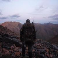 A Canol Outfitters guide walking among the towering mountains of the Mackenzie in the NWT.