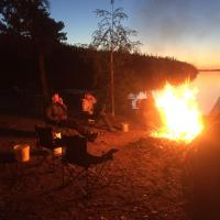 Three men sitting around a fire at North Star Resort on the sandy beach in the NWT.