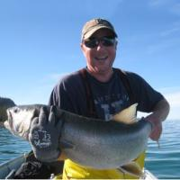 A fisher man holding up a huge lake trout caught in the Great Slave Lake at Trophy Lodge in the NWT.