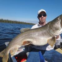 Big lake trout caught and held up by fisherman at Lac La Martre in the Northwest Territories.