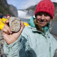 a hiker holds up a fossil in nahanni national park reserve