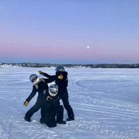 Destination NWT visitors posing on a frozen lake in Yellowknife, NWT.