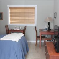 A guest room with a side table and a bed in the Willows Inn motel in Fort Simpson, Northwest Territories.