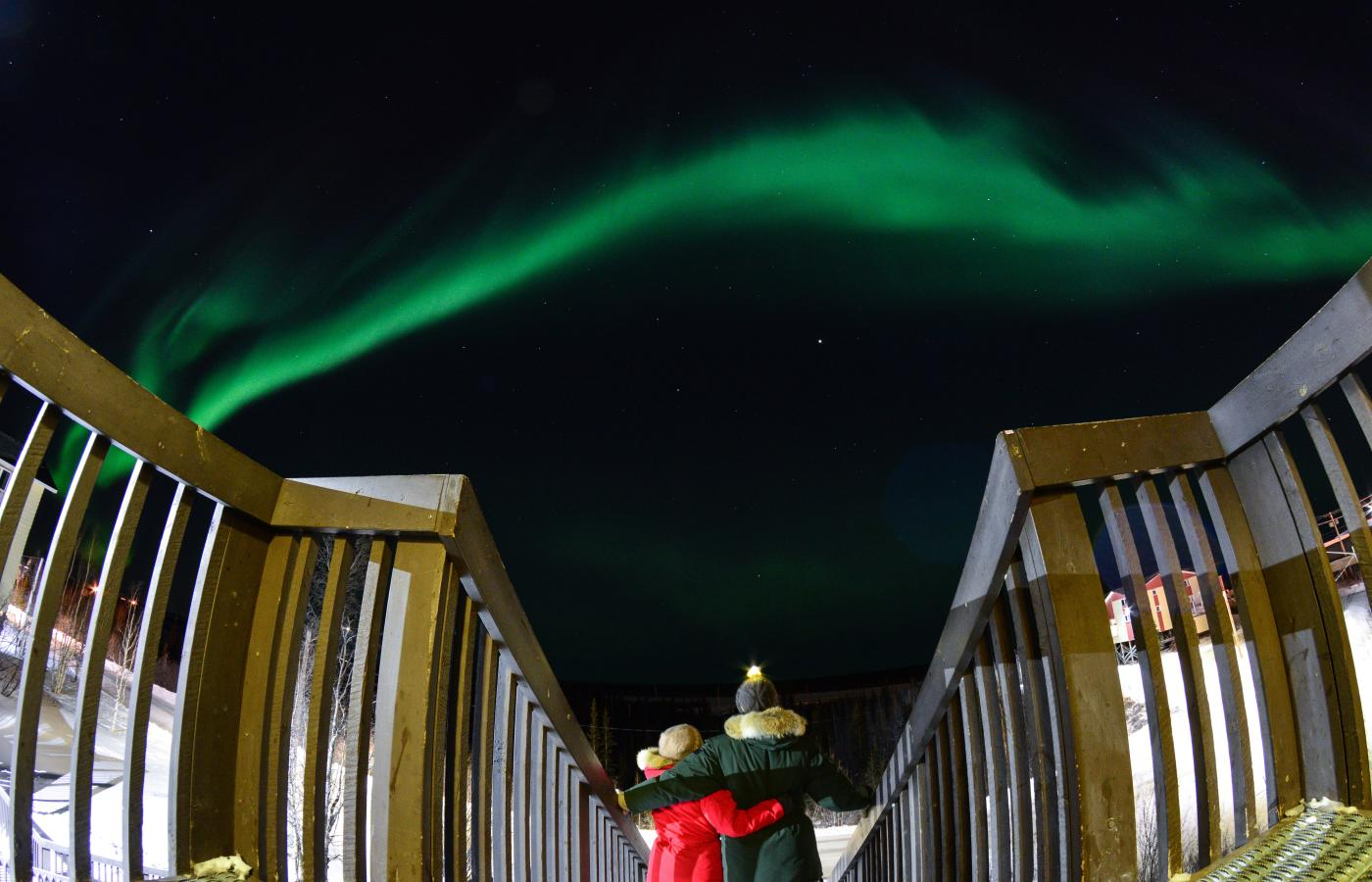 couple looking up at Aurora Northern Lights Inuvik romance