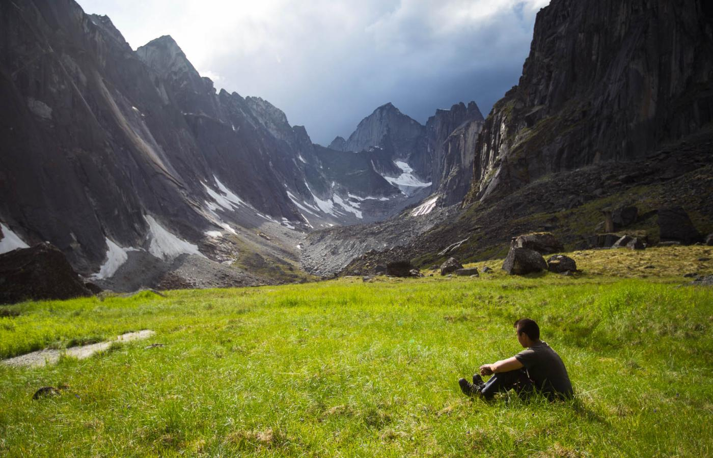 A person relaxes on a meadow of green at the foot of craggy mountains