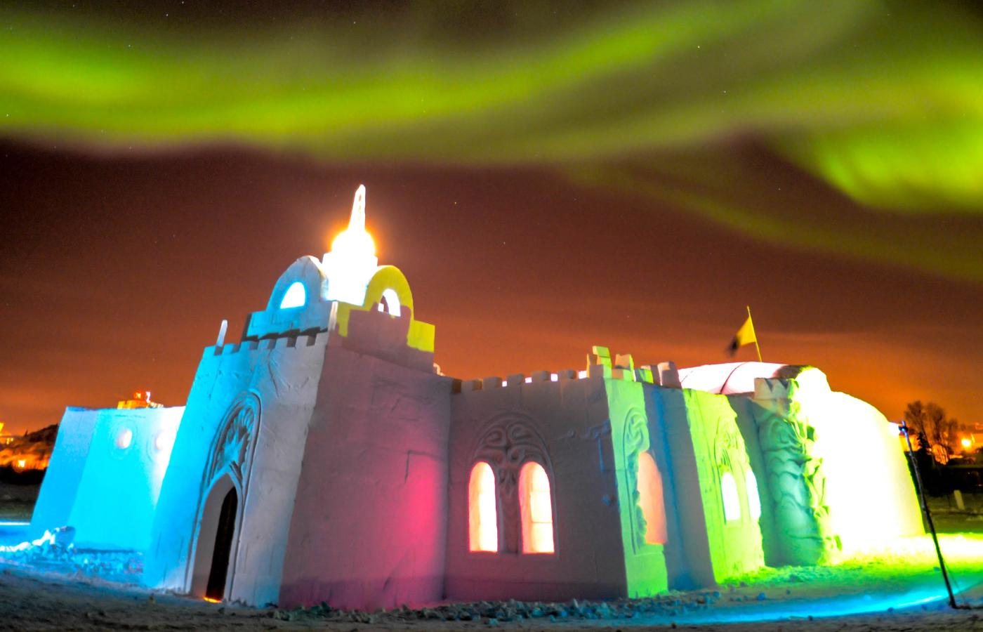 The SnowKing Castle shines in blue red and green colours under the shining Northern Lights in the month of March