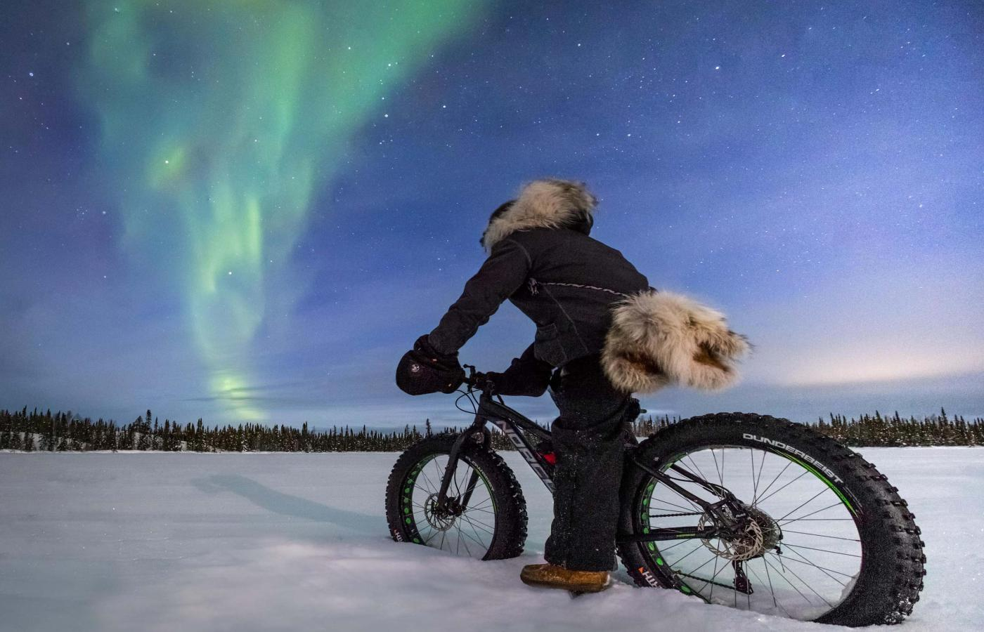 Fat-biking across a frozen lake in Canada's Northwest Territories as the Northern Lights dazzle overhead.