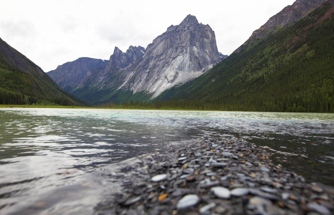 A mountain peak rises above a glacier lake in the Nahanni