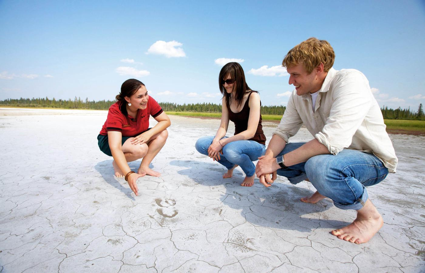 A Parks Canada staff examines the salt plains with two tourists