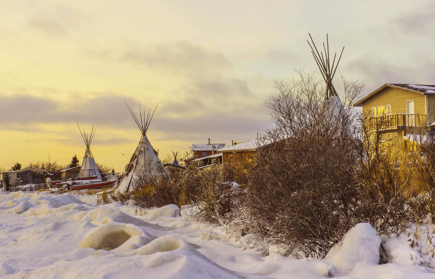 Dene community with houses and teepees in the winter under the sunset