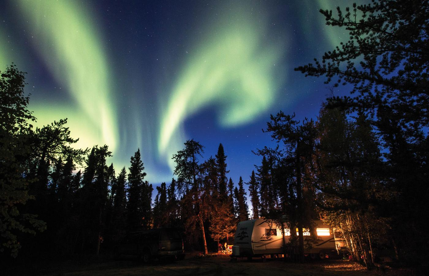 The Aurora fills the sky over an RV parked in a campground in the Northwest Territories