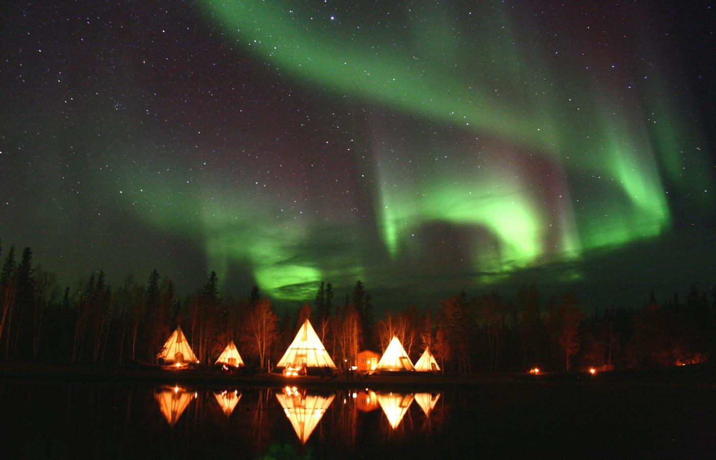 The Northern Lights fill the sky over Aurora Village and lit teepees.
