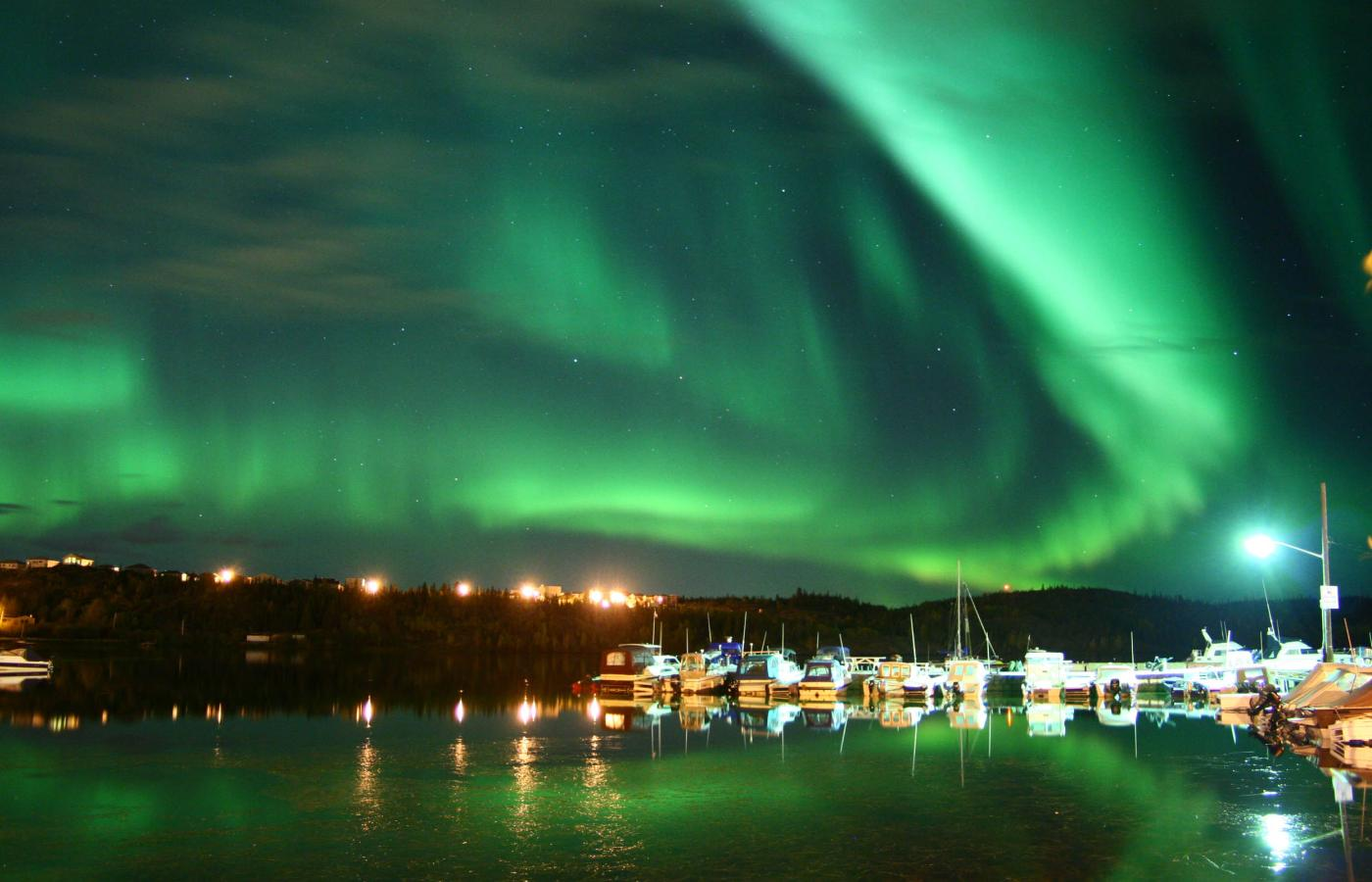 The Aurora fills the sky at Aurora Village in the NWT and is reflected in a lake