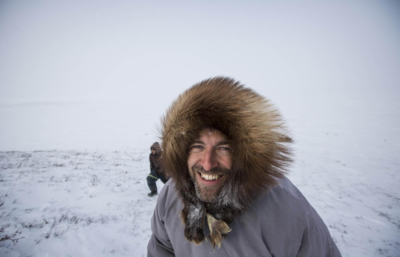 Man in parka trimmed with fur on the tundra in the NWT