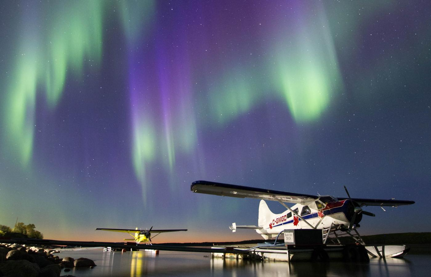 Curtains of Northern Lights blaze out in the sky over a floatplane docked on a river in the NWT